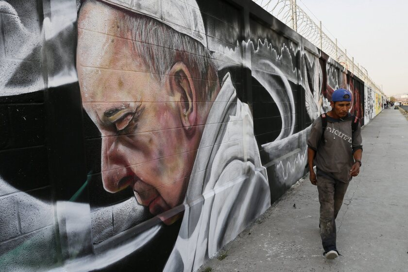 A man walks past a mural painted in honor of Pope Francis' visit in Ecatepec, Mexico.