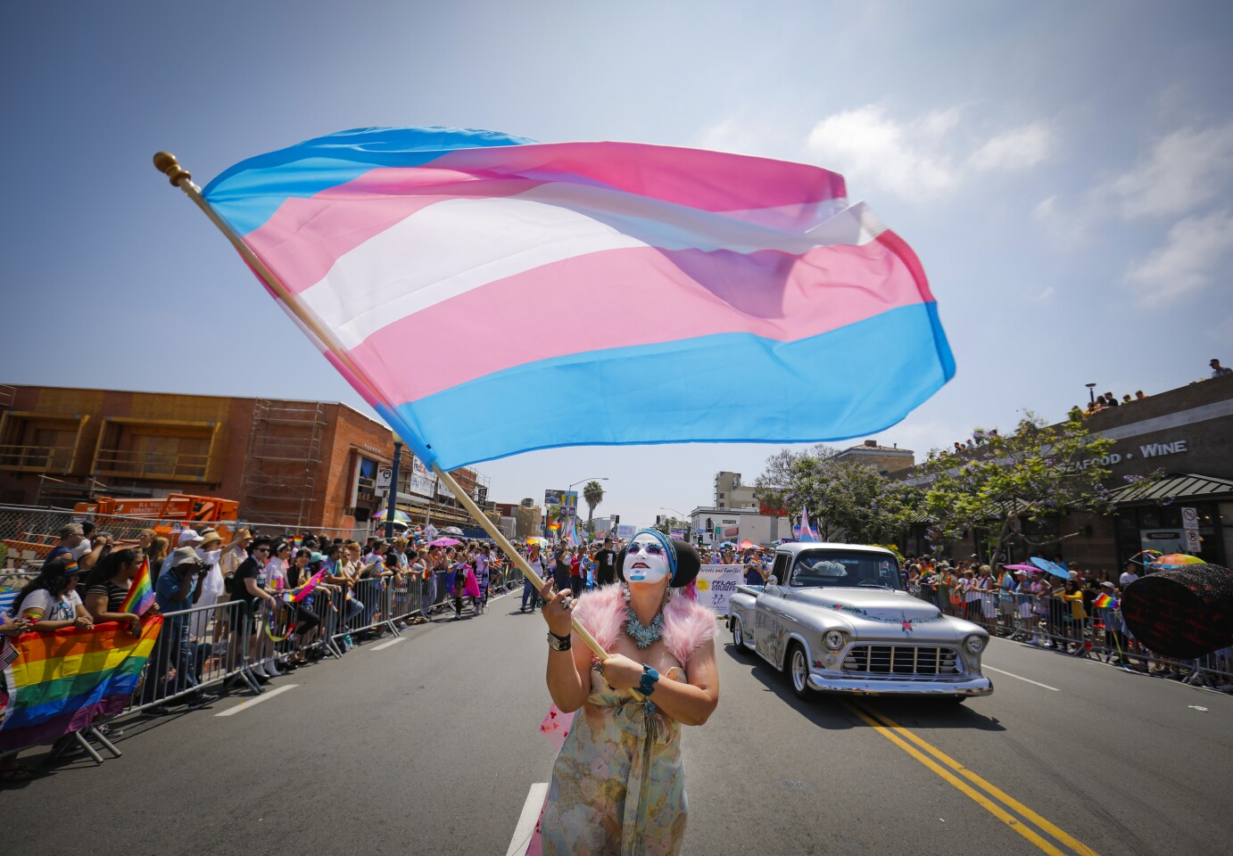 Sister Yesate of the Sisters of Perpetual Indulgence waves a transgender flag while walking the annual San Diego Pride Parade.
