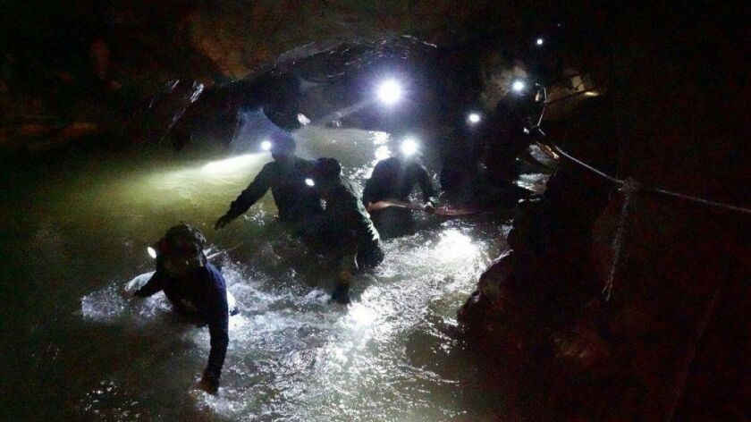 This photo released by the Royal Thai Navy shows Thai Navy Seals navigating a flooded section of the Tham Luang Nang Non cave to search for 12 boys and their soccer coach.