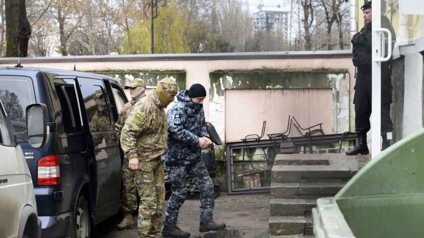 A Ukrainian sailor, center, is escorted by Russian intelligence agency FSB officer, left of him, to