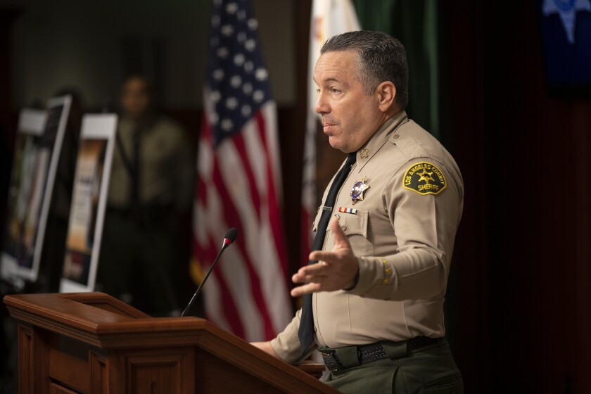 Sheriff Alex Villanueva gestures as he speaks at a lectern during a news conference