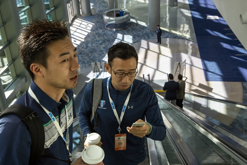 Kensuke Nakata, left, who works for Dome Corporation (Under Armour Japan) and Shinzo Yamada, senior associate athletic director at the University of Tsukuba, take the escalators to a session during the NCAA 2020 convention.