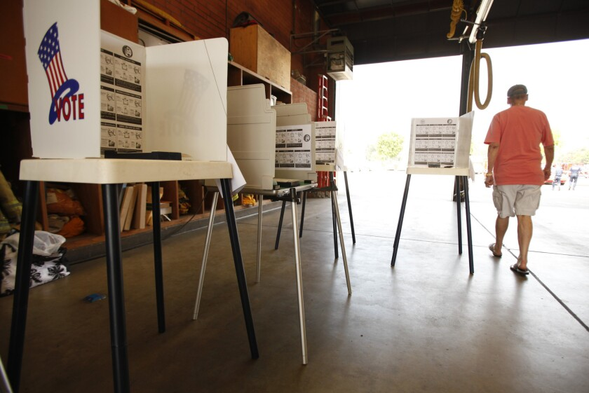 Jay Goldfard of Encino walks past empty voting booths after bringing his mail ballot to the Los Angeles City Fire Station 88 in Sherman Oaks on Tuesday, May 21, 2013.