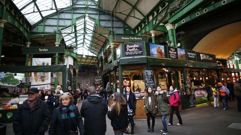 Shoppers stroll through Borough Market in London.