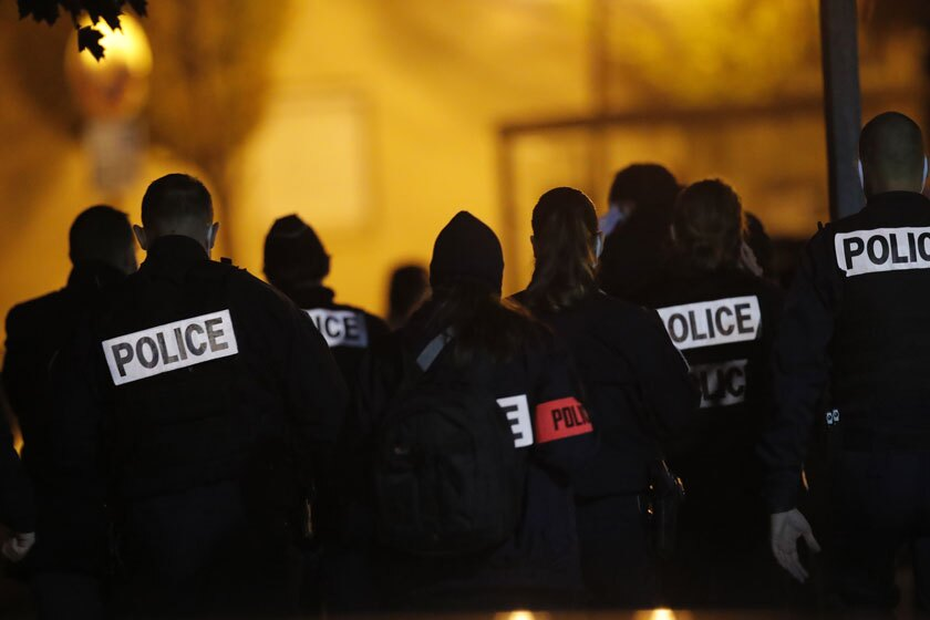 French police officers gather outside a high school near Paris after a history teacher was beheaded Friday.