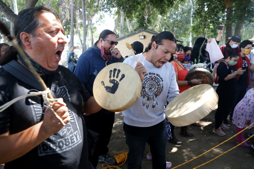 Activists sing and play drums after toppling the statue of Father Junipero Serra in downtown L.A.