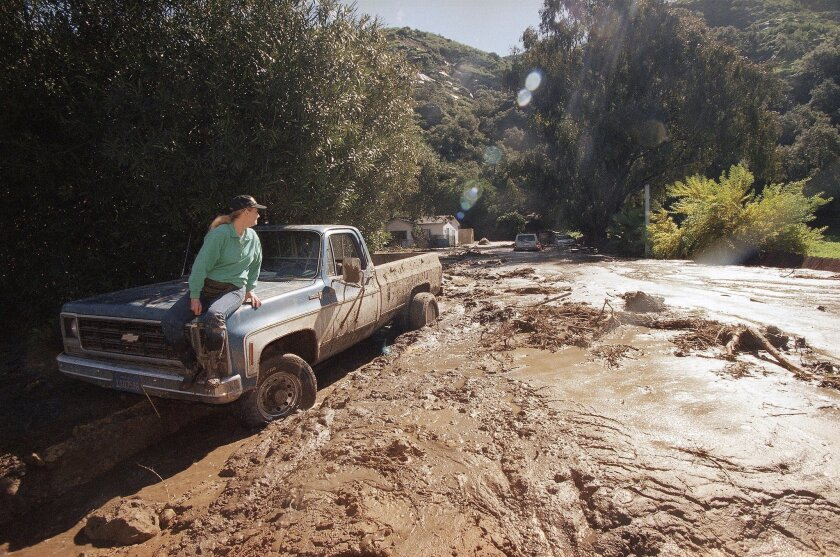 In this Feb. 24, 1998 file photo, a woman waits for a tow truck on the hood of her brother's pickup after a wall of mud unleashed by an El Nino storm plowed down Laguna Beach Canyon Road in Orange County, forcing her to evacuate her home, in background. (AP Photo/Nick Ut, File)