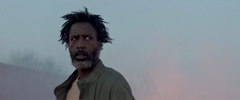 """A man looks apprehensively to his left in movie """"Akilla's Escape."""""""