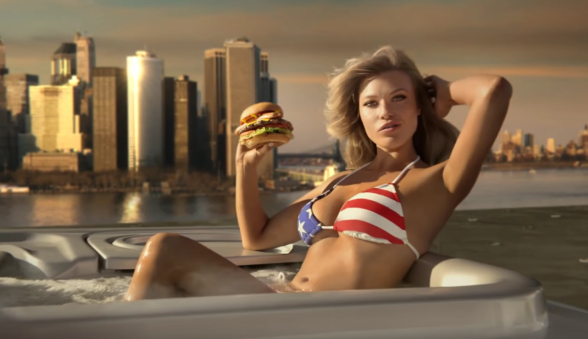 Carl's Jr. employee least likely to be replaced by a robot? Scene from a TV commercial for CKE's Most American Thickburger, which loaded potato chips and a hot dog onto a half-pound burger on a bun: 1,190 calories, not including fries and a shake.