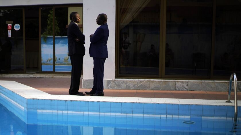 Members of the Congolese opposition coalition Lamuka talk while waiting for a statement to be issued on the timing of the release of the presidential election results in Kinshasa on Saturday.