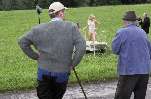 Two farmers watch the German farmer calendar shooting with model Veronika.