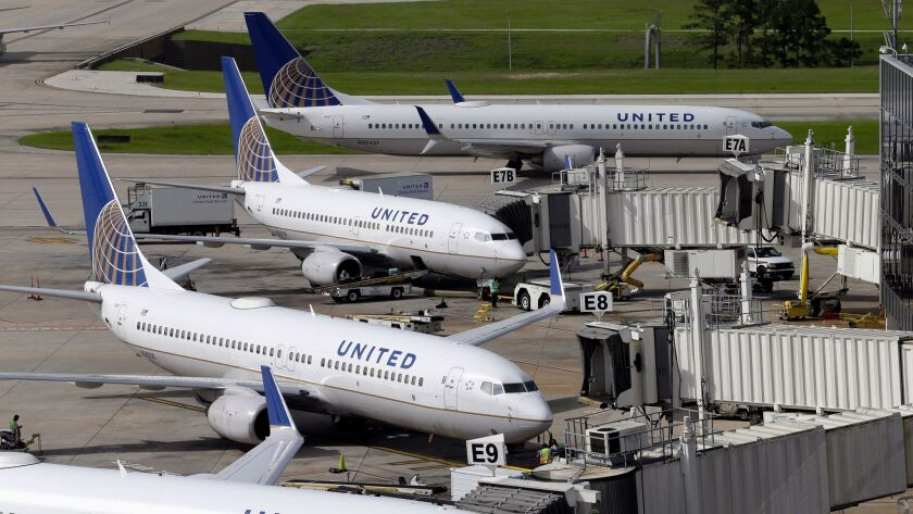 FILE - In this July 8, 2015, file photo, United Airlines planes are parked at their gates as another
