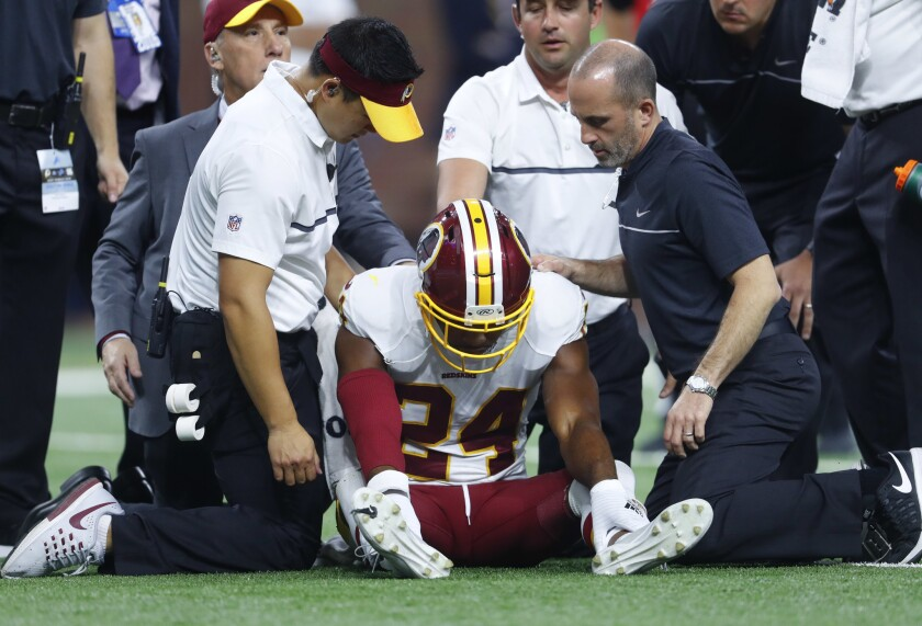 Washington Redskins cornerback Josh Norman is attended to by trainers against the Detroit Lions during a game in Detroit on Oct. 23, 2016. Norman left the game with a concussion.