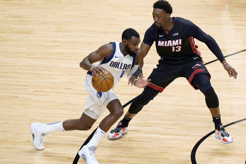 Dallas Mavericks forward Tim Hardaway Jr. (11) drives up against Miami Heat center Bam Adebayo (13) during the first half of an NBA basketball game, Tuesday, May 4, 2021, in Miami. (AP Photo/Wilfredo Lee)