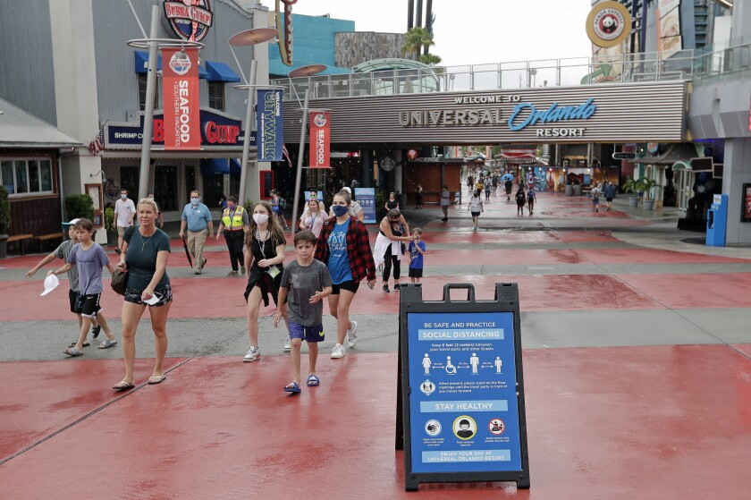 In this Wednesday, June 3, 2020 photo, signs about social distancing and other protocols are seen about the theme park as guests walk by at Universal Orlando Resort Wednesday, June 3, 2020, in Orlando, Fla. The theme park reopened for season pass holders and will open to the general public on Friday, June 5. (AP Photo/John Raoux)
