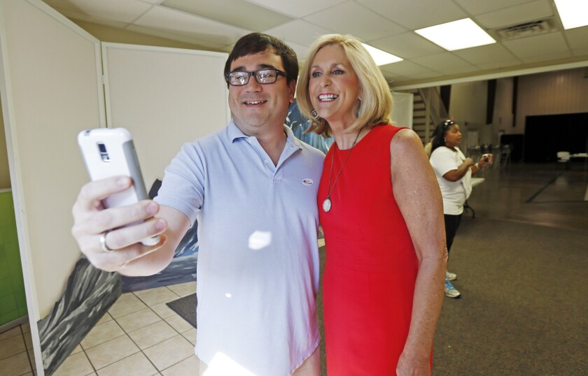 Morgan Bondurant uses his smartphone to take a selfie of himself and state Treasurer Lynn Fitch as they exit the voting precinct after voting in Madison, Miss., on Aug. 4.