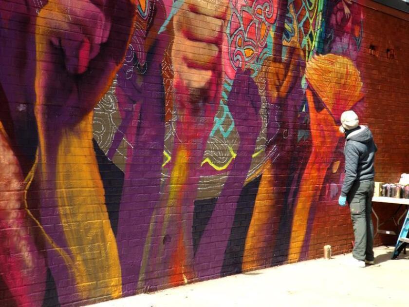 """El artista californiano Alexander Tadlock da los últimos retoques sobre su mural titulado """"México está en dónde estás tú"""" en el barrio hispano de La Villita, en Chicago (Illinois). EFE"""