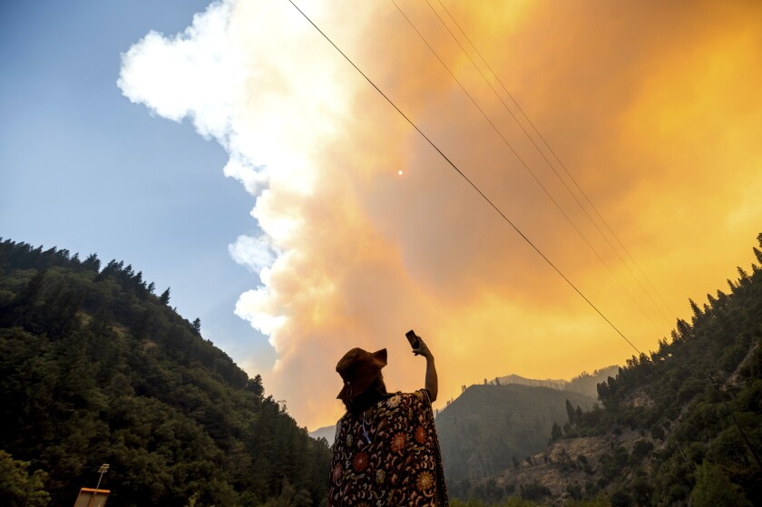 A woman takes a video as the Dixie fire burns in Plumas National Forest.