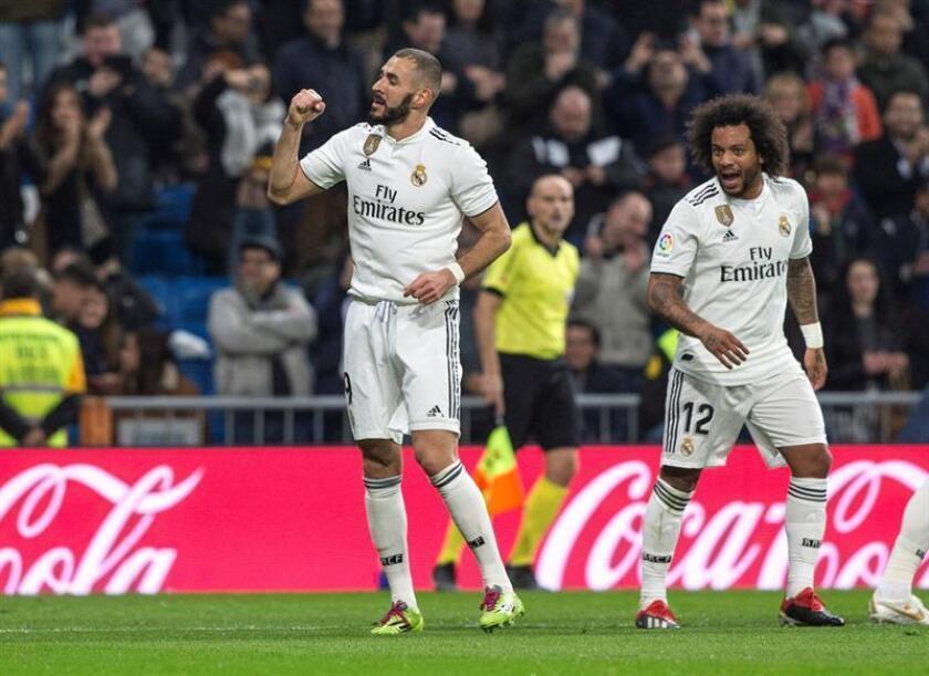 El delantero francés del Real Madrid Karim Benzema (i), celebra con sus compañero Marcelo Vieira el primer gol de su equipo ante el Rayo Vallecano, durante el partido correspondiente a la jornada 16 de LaLiga Santander disputado en el estadio Santiago Bernabéu. EFE