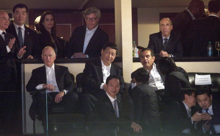 Xi Jinping, then the vice president of China, speaks with then-Los Angeles Mayor Antonio Villaraigosa while Jerry Brown, then governor of California, watches a game between the Lakers and the Suns at Staples Center in 2012. At top right is Jeffrey Katzenberg, then-CEO of DreamWorks Animation, who used his ties to California politicians — and to then-Vice President Joe Biden — to lobby Xi for access to the Chinese market.