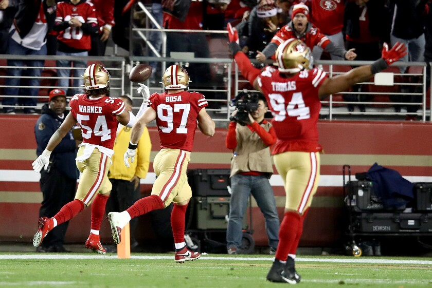 49ers linebacker Fred Warner flips the ball in the end zone after returning an interception 46 yards for a touchdown late in the second quarter.
