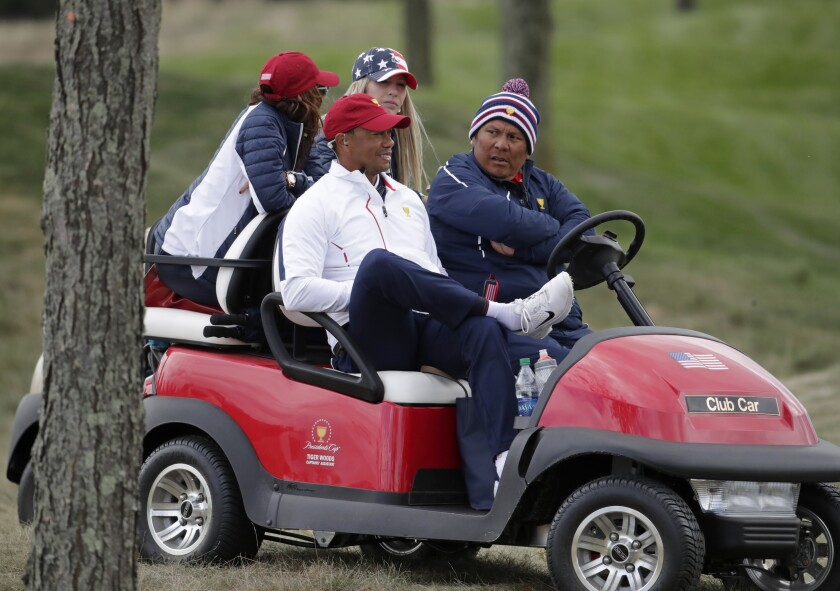 FILE - In this Sept. 30, 2017, file photo, Tiger Woods watches play on the fourth hole during the four-ball golf matches on the third day of the Presidents Cup golf matches at Liberty National Golf Club in Jersey City, N.J. The role of Presidents Cup captain typically is reserved for players in the twilight of their careers. Nothing is typical about Tiger Woods. (AP Photo/Julio Cortez, File)
