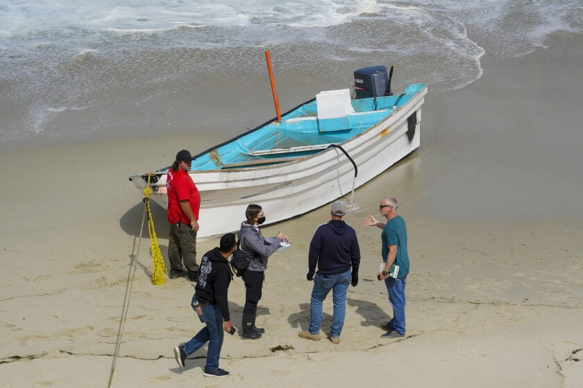 Investigators near the Children's Pool in La Jolla look over a small boat on the beach used in a smuggling attempt.