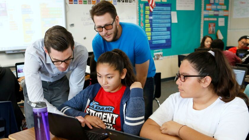 Adams Elementary School Principal Gabriel Del Real, left, and CodeCampus instructor Nathan Valdez go over coding with students Alexis Pellegrin and Laisha Burciaga, right, at the Costa Mesa campus Friday.