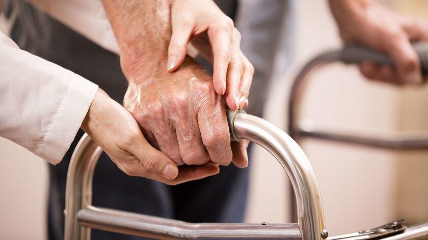 Female doctor helps senior man patient use walker. Holding hands.