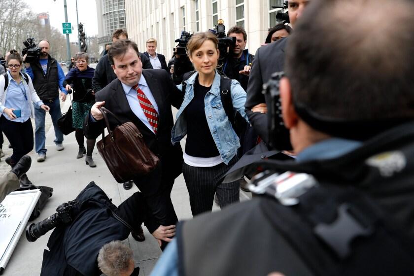 Varios fotógrafos se caen al suelo cuando la actriz Allison Mack abandona el Tribunal Federal hoy, en Brooklyn