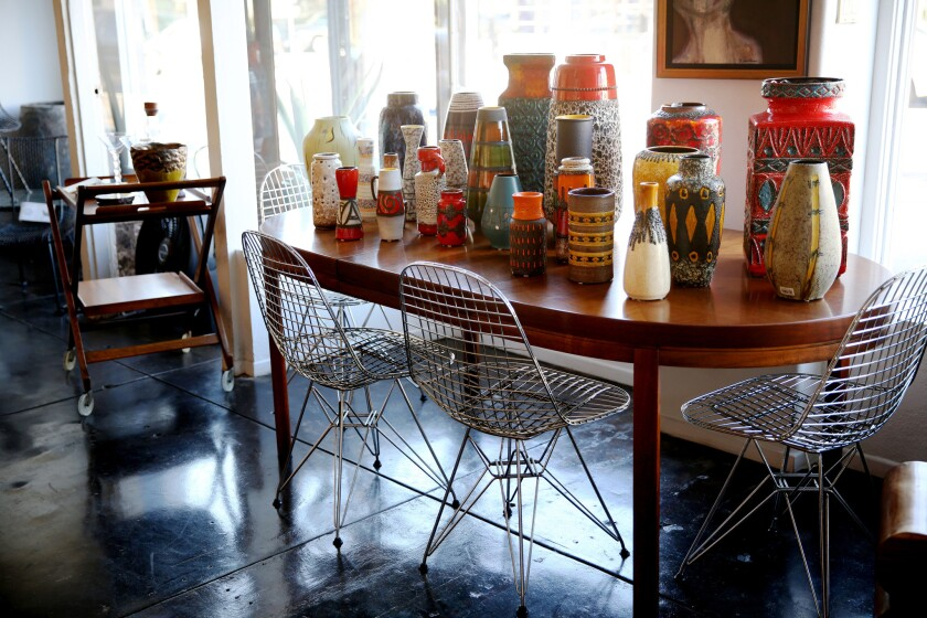 West German pottery decorates a tabletop at Trebor/Nevets. A set of 4 Eames Eiffel Tower chairs by Herman Miller sit around the table.