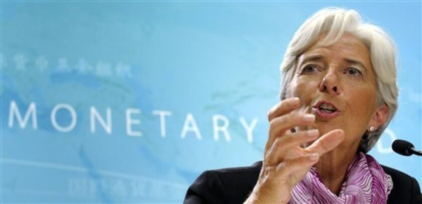 """FILE - In this July 6, 2011, file photo International Monetary Fund (IMF) Managing Director Christine Lagarde speaks at her first news conference at IMF headquarters in Washington. In an interview broadcast Sunday July 10, 2011, Lagarde said she foresees """"real nasty consequences"""" for the U.S. and global economies if the U.S. fails to raise its borrowing limit. It would cause interest rates to rise and stock markets to fall, she said, and that would threaten an important IMF goal, which is preserving stability in the world economy. (AP Photo/Susan Walsh, File)"""