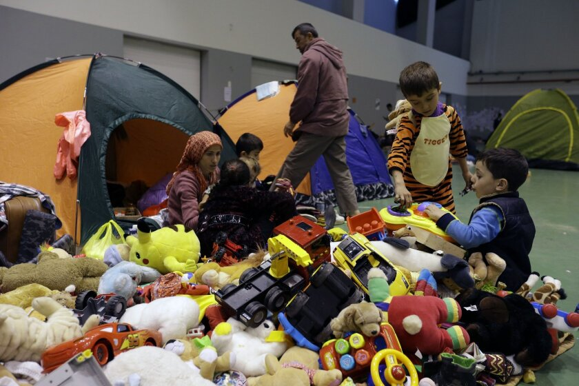 Boys play with toys distributed by volunteers as family members sit outside their tents at the Galatsi Olympic Hall in Athens, Wednesday, Nov. 4, 2015. The disused facility, which used during the Athens Olympics 2004, reopened a month ago for migrants as more than 600,000 people have arrived in Gre