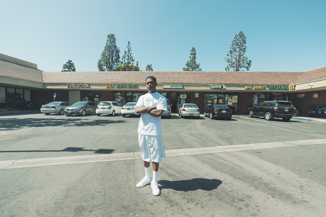 Barrington Darius stands in front of a small plaza wearing a white Pro Club t-shirt, white shorts, socks, and shoes.