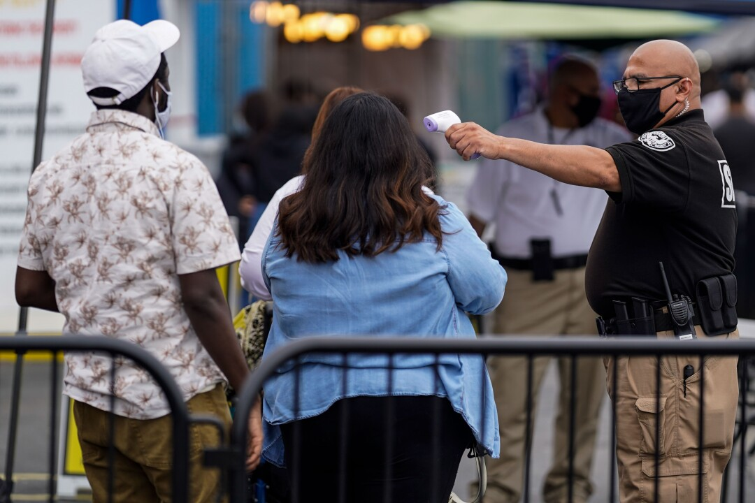 A security guard checks the temperature of guests entering the Santa Fe Springs Swap Meet.