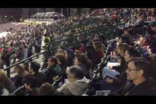 People attend vigil for shooting victims at San Manuel Stadium in San Bernardino