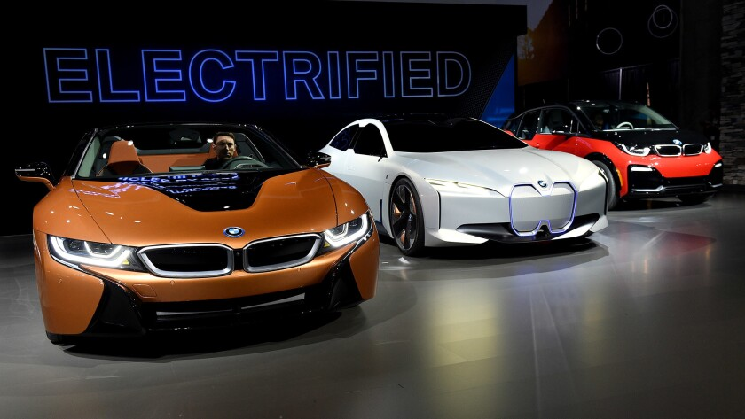 Among the electric cars at the 2017 LA Auto Show are a BMW 2019 i8 Roadster plug-in hybrid, left, the BMW i Vision Dynamics electric concept car and a Mini Cooper plug-in hybrid.