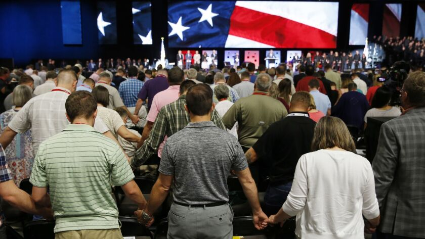 FILE - In this June 12, 2018 file photo, people pray for America at the 2018 annual meeting of the S