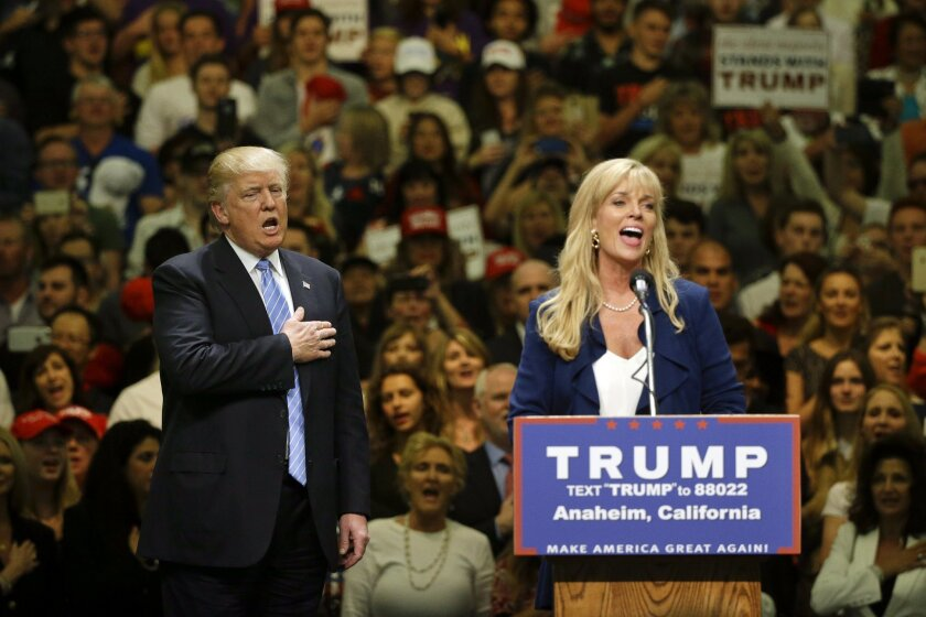 Republican presidential candidate Donald Trump, left, sings the National Anthem with unidentified woman during a rally at the Anaheim Convention Center, Wednesday, May 25, 2016, in Anaheim, Calif. (AP Photo/Jae C. Hong)