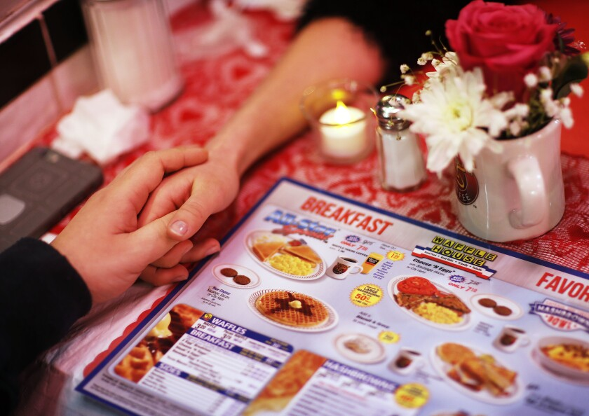 FILE - In this Feb. 14, 2018, file photo Valerie Deschamps-Goren, right, holds hands with Basil Gravanis while dining at a Waffle House restaurant decorated for Valentine's Day in Atlanta. Valentine's Day: a day to celebrate your partner or a day to celebrate yourself. And while it may not sound romantic, this time of year is also an opportunity to show your finances some love. (AP Photo/David Goldman, File)