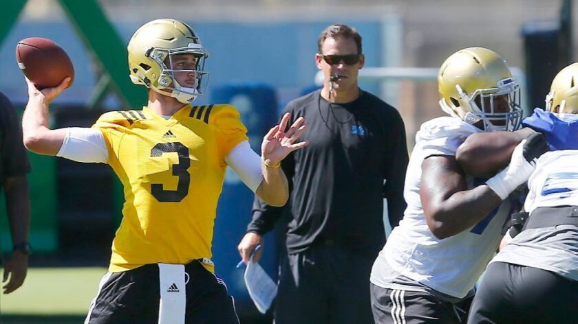 UCLA Coach Jim Mora watches as quarterback Josh Rosen throws a pass during a training camp practice on Aug. 15.