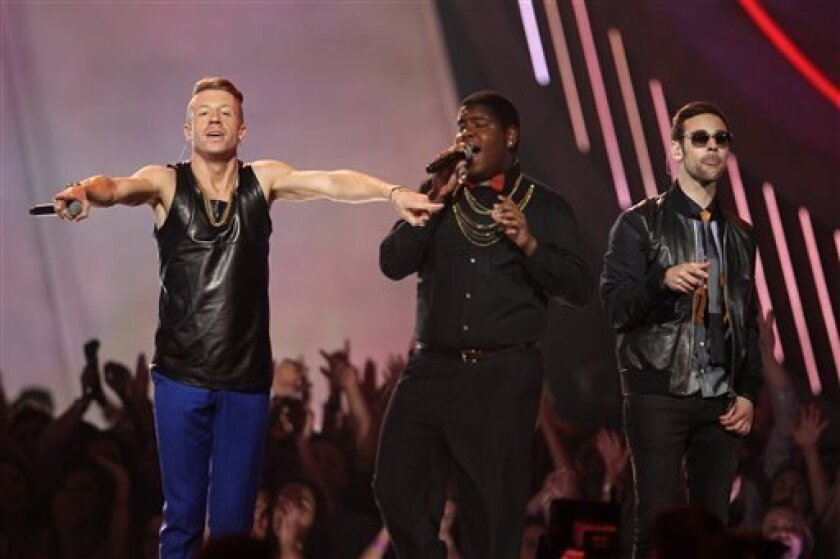 """FILE - This April 14, 2013 file photo shows Macklemore, left, and Ryan Lewis, right, performing """"Can't Hold Us"""" with Ray Dalton at the MTV Movie Awards in Sony Pictures Studio Lot in Culver City, Calif. The song was the top streamed track on Spotify from Monday, April 15, to Sunday, April 21. (Phot"""