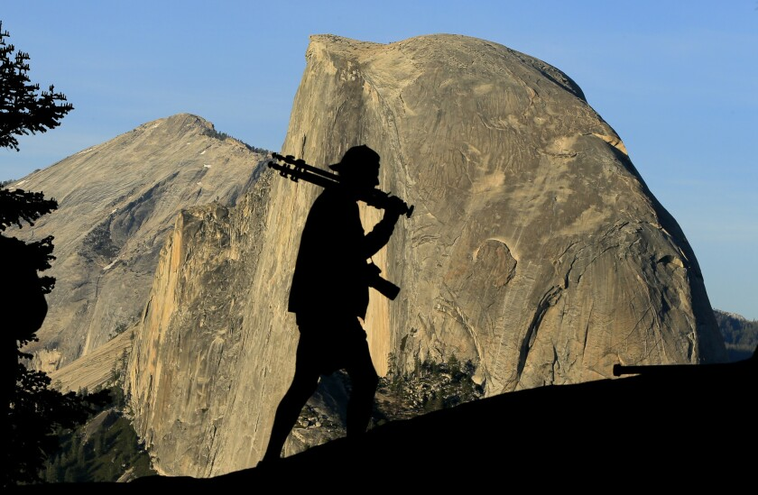 A man silhouetted in front of Yosemite's Half Dome.