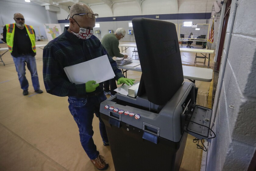 Poll worker Eric Boson submits absentee ballots during the Wisconsin 7th District special election on Tuesday in Marshfield, Wisconsin.