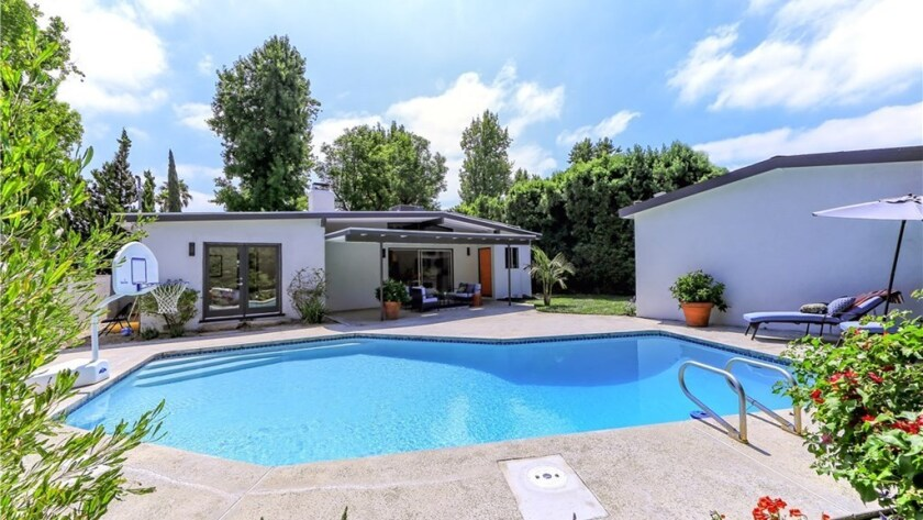 The house sits on a 6,000-square-foot lot with a swimming pool, a covered patio and a two-car garage.