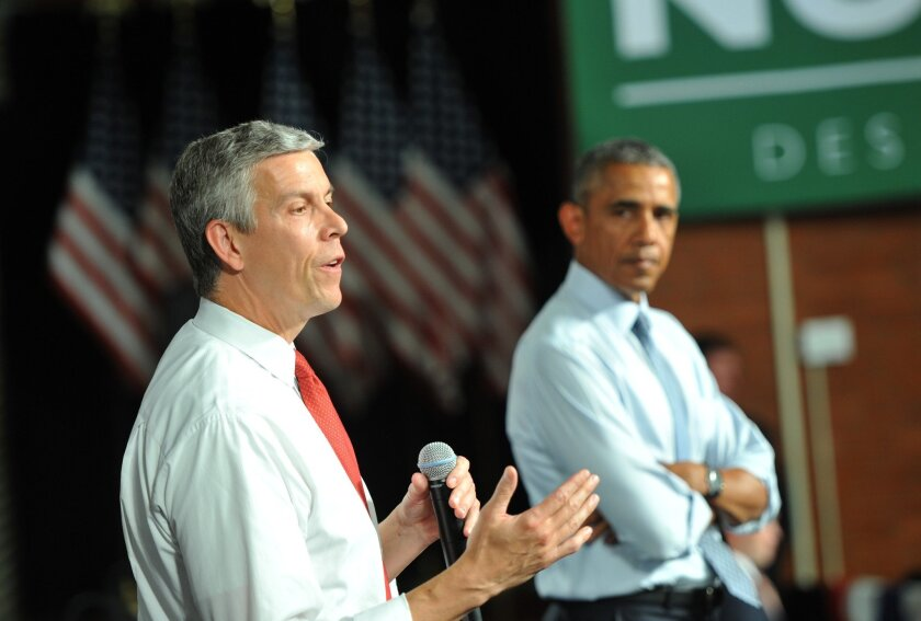 U.S. Secretary of Education Arne Duncan, left, and President Obama attend a town hall meeting in Iowa last month about student loans. Duncan said Friday that he will step down from his post in December.
