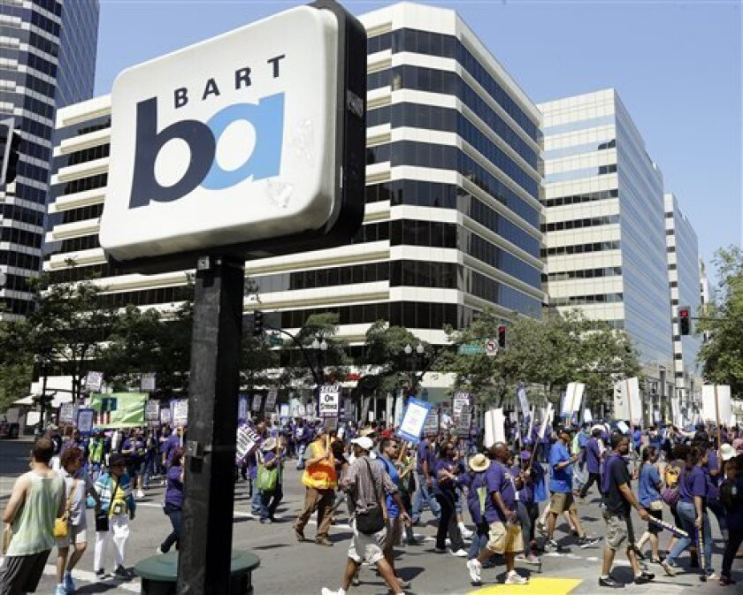 In this file photo from Monday, July 1, 2013, striking Bay Area Rapid Transit workers picket as they close the intersection of 14th & Broadway on Monday, July 1, 2013, in downtown Oakland, Calif. San Francisco Bay Area commuters braced for the possibility of another train strike as the Bay Area Rapid Transit agency and its workers approached a deadline to reach a new contract deal. The two sides were set to resume negotiations at noon on Thursday, Aug. 1, but did not appear close to an agreement
