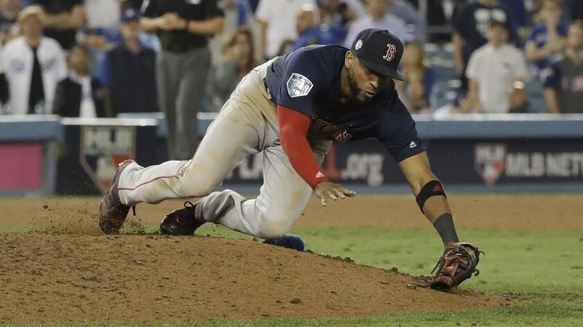 Boston Red Sox pitcher Eduardo Nunez trips on the mound after catching a pop up fly by Los Angeles D
