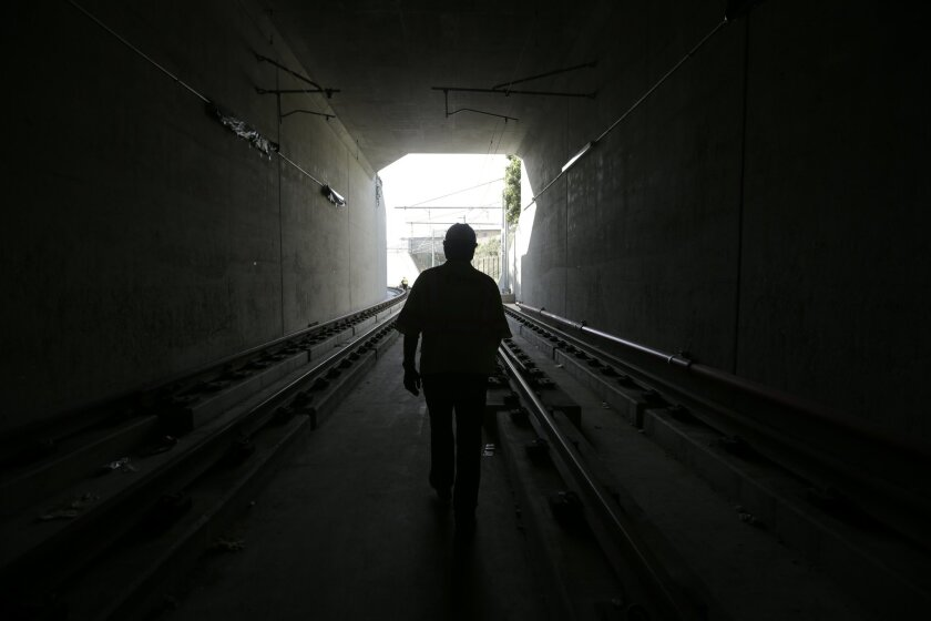 In this Friday, May 1, 2015 photo, senior project manager David Walker walks through a railway tunnel under construction in Los Angeles, part of the Metro Expo Line extension project connecting Culver City and Santa Monica, Calif. L.A. has embarked on a transportation building binge funded largely