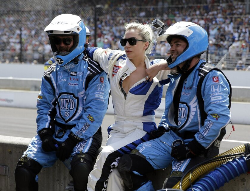 Lady Gaga, center, poses for a photo with members of the Carlos Munoz pit crew during the 100th running of the Indianapolis 500 auto race at Indianapolis Motor Speedway in Indianapolis, Sunday, May 29, 2016. (AP Photo/Jeff Roberson)